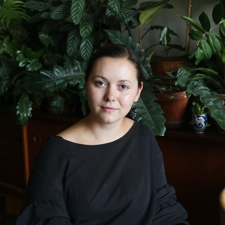 Frau sitzt zwischen Pflanzen