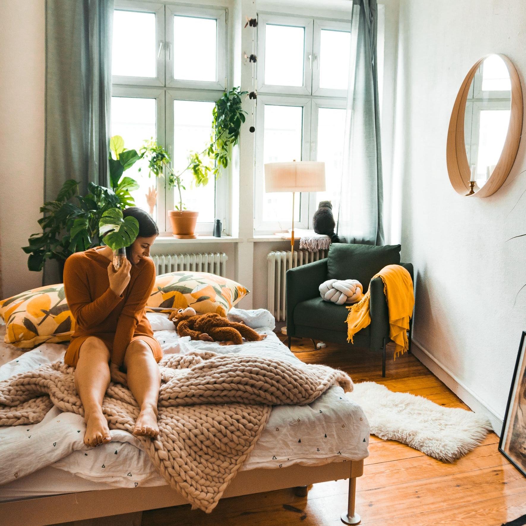 Frau sitzt auf einem Bett mit einem Blatt in der Hand